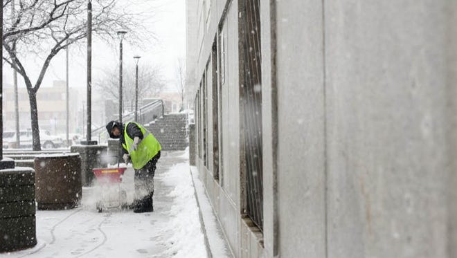 A Camden City Hall employee salts a walk way during a heavy snow, Monday, February 3, 2014 in Camden.