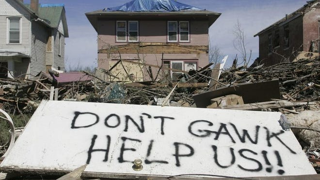 "A message reading ""Don't Gawk, Help Us!!"" was spray painted on a door, sitting in the debris pile along the boulevard on Iowa Avenue in Iowa City."