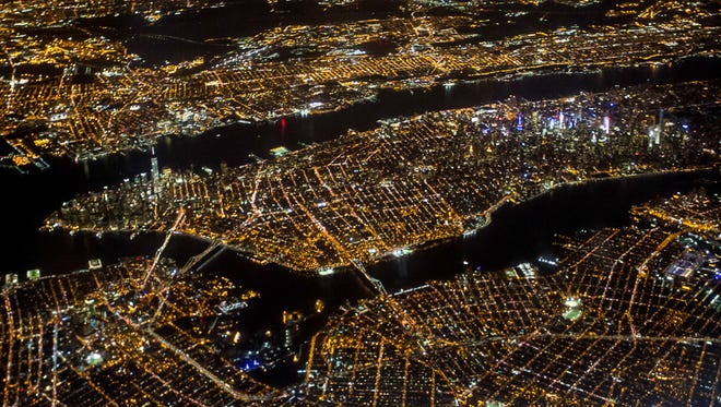 The island of Manhatten radiates light as a Delta flight passes overhead, due to land at New York's JFK Airport.