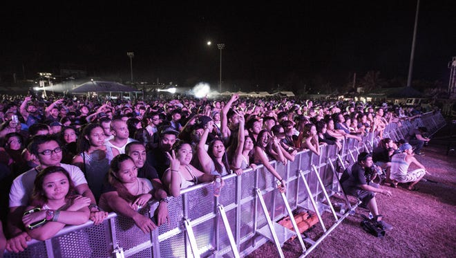 Concert-goers cheer on the musical act performing during a previous Guam Live International Music Festival at Paseo Stadium.