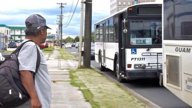 A passenger prepares to board a Mass Transit bus outside the Nieves M. Flores Memorial Public Library in Hagatna on Aug. 8, 2013. Pacific Daily News file photo