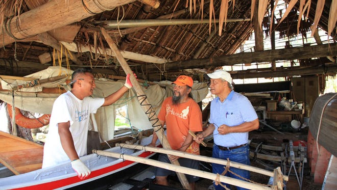 Members of the Tasi group, from left, Dio Sapinoso, Nash Camacho, and Louie Wabol discuss fixing the mast at Paseo on Monday, May 25.