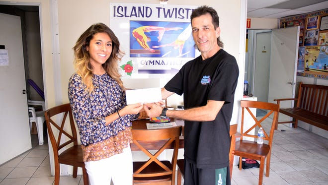 Shieh Su Ying Scholar-Athlete 2015 Award for Outstanding Community Service winner Christina Francisco hands a $1,000 check to co-owner and coach of Island Twisters Derrick Heath yesterday in Tamuning. The check will go toward much-needed gymnastics equipment and will benefit over 100 children and possibly hundreds more through the years, said Heath.