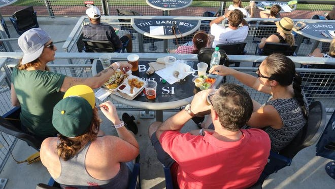 Suzanne Hertl, left, Colleen Cain, Tim Mayes and Gina Battaglia dine at one of the four-top tables at The Band Box at First Tennessee Park.