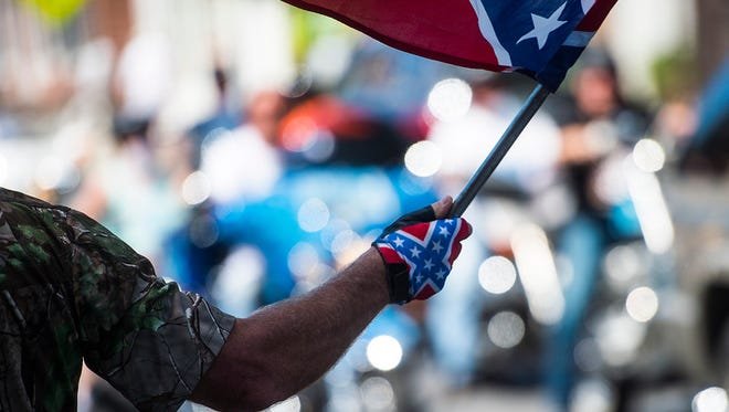"""A protester waves the Confederate flag along Baltimore Street in downtown Gettysburg on Saturday July 11, 2015.   Shane Dunlap - The Evening Sun"""