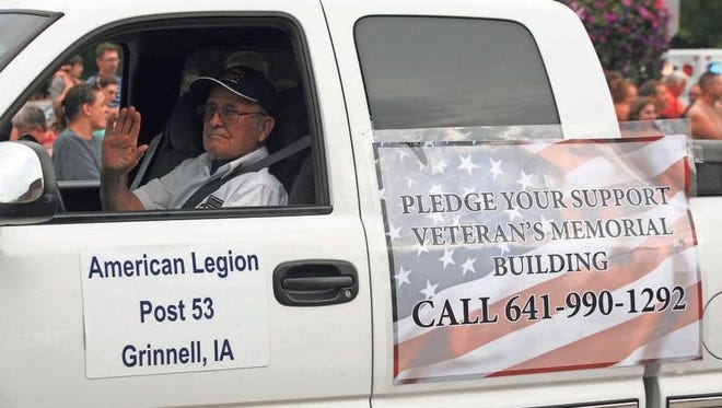 George Fowler with Grinnell American Legion Post 53 rolls along Broad Street during the Grinnell Homecoming Parade with a sign seeking community support for saving the Grinnell Veterans Building. A task force was created this summer to raise the nearly $1 million needed to save the historical building.