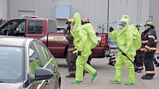 Grinnell firefighters wearing haz-mat gear, prepare to go inside Purfoods in Grinnell to locate an ammonia refrigerant leak in the building. At least 11 were injured during the incident that occurred on Monday, Oct. 5.