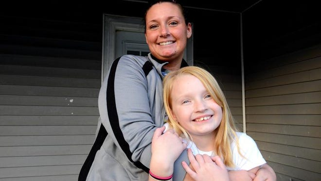 Melanie Newcombe and daughter Teegan, 9, stand on the porch of their home  in Ionia onTuesday. Newcombe's husband Brandon, a Marine, bought the house for the family to fix up and live in. Brandon died on May 16, 2014, but two Michigan non profits - Faith Works Michigan and Operation: Come H.O.M.E. - teamed up to finish the work on the house after he died.