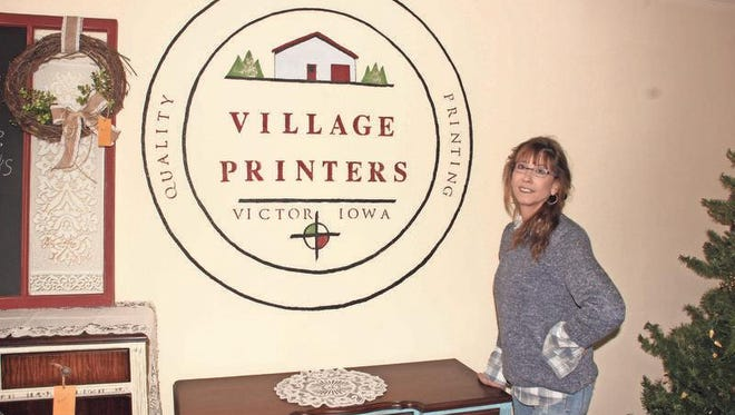 Deb Kurovski proudly shows off the logo of Village Printers, which was painted on this wall earlier this fall.