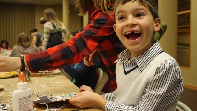 Lucas Weber creates a snowman using a paper plate and shredded paper during Day at the Museum, featuring crafts by Good Garbage! at the Carnegie Center for Art & History in New Albany on Wednesday.