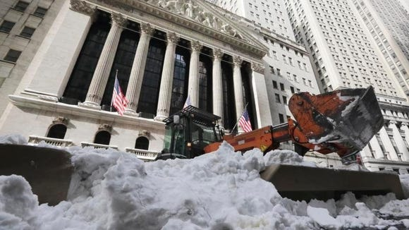 A front end loader removes snow in front of the New York Stock Exchange, Monday, Jan. 25, 2016.