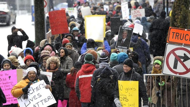 Burton International Academy computer advanced teacher Denice McGee, bottom left, holds a sign as she and other protesters wait to cross the street Wednesday, Jan. 20, 2016, in Detroit. Most of Detroit's public schools closed for the day on Wednesday due to teacher absences, as disgruntled educators stepped up efforts to protest the governor's plans for the district, its ramshackle finances and dilapidated buildings. (Todd McInturf/Detroit News via AP)  DETROIT FREE PRESS OUT; HUFFINGTON POST OUT; MANDATORY CREDIT  MBO  (REV-SHARE)