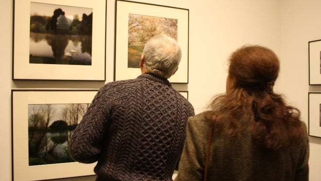 "Michael and Patricia Tate look over a series of watercolor-esque photos by created by artist Lynn Geesaman in 1993 during the exhibit opening for ""Bernheim:  A Natural Muse"" at the Carnegie Center for Art & History in New Albany on Friday."