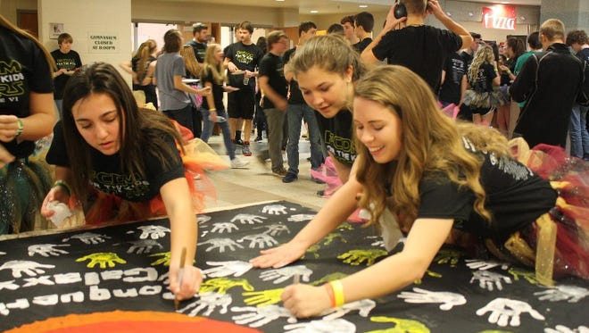 Sophomore Aubry Fonseca, left, and seniors Raini Heitz and Emma Platt, place their handprints on a banner that will be sent to the hospital during the 6th annual Floyd Central Dance Marathon benefiting Riley Children's Hospital at Floyd Central High School in Floyds Knobs on Saturday.