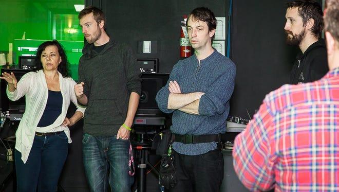 "Jill Murphy Long works with crew members in the newsroom scene of her film ""Meltdown."""