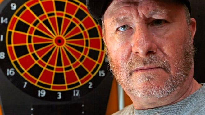 Lacey resident Rich Koppenjan, who is blind, stands before his audio dartboard. Koppenjan is one of the top throwers on the audio darts circuit.