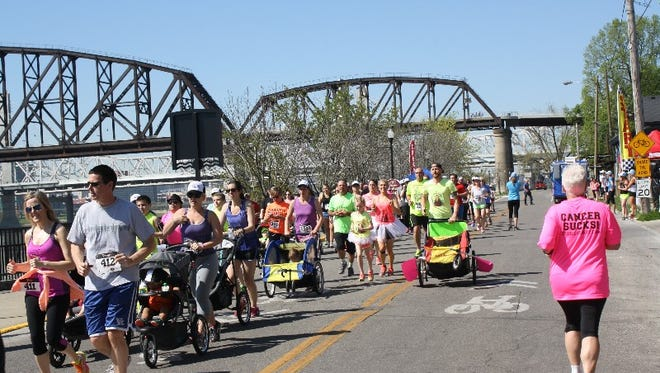 A runner in the competitive wave of the event passes those just heading out in the noncompetitive event during the 5K Donut Challenge along the Jeffersonville waterfront on Sunday.  April 17, 2016