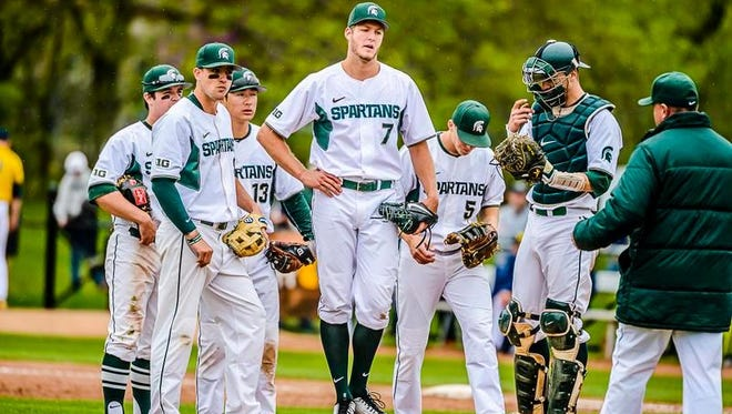 MSU pitcher Ethan Landon, 7, reacts as he is about to be pulled from the Spartns game with Michigan by MSU Head Coach Jake Boss, right, with 2 outs in the top of the 9th and MSU leading 7-6. Landon was pulled 1 out short of a complete game.