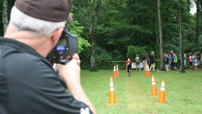 Kevin Fisher, Charlestown High School's school resource officer,  uses a radar gun to time a participant as he runs during the inaugural Heroes Camp hosted by the Clark County Sheriff's Office on Wednesday.