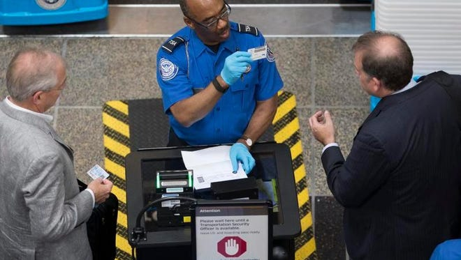 An employee of the Transportation Security Administration (TSA) inspects travelers' identification.