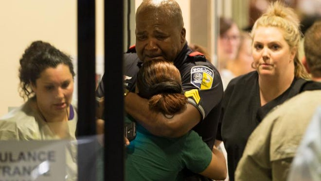 A Dallas Area Rapid Transit police officer receives comfort at the Baylor University Hospital emergency room entrance Thursday, July 7, 2016, in Dallas. Police say one rapid-transit officer has been killed and three injured when gunfire erupted during a protest in downtown Dallas over recent fatal shootings by police in Louisiana and Minnesota. (Ting Shen/The Dallas Morning News via AP)