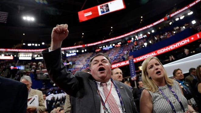 Delegates react as some call for a roll call vote on the adoption of the rules during first day of the Republican National Convention in Cleveland, Monday, July 18, 2016.