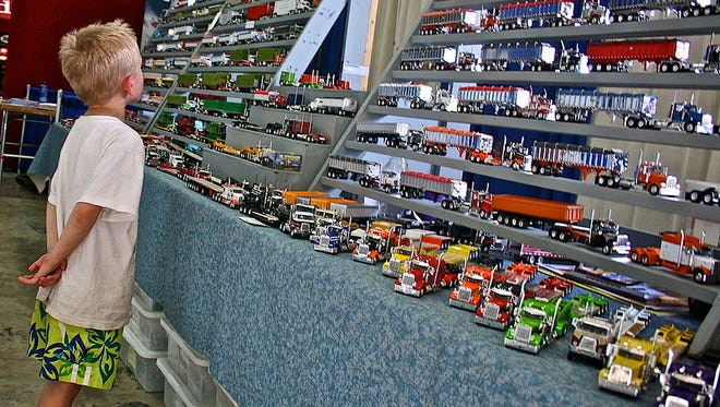 A young boy examines a collection of model semi trailers.