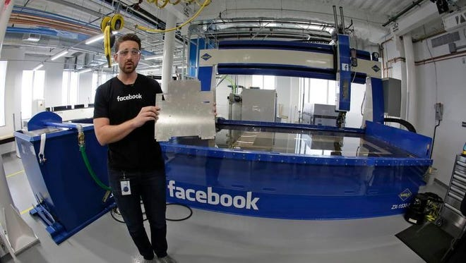 Model maker Spencer Burns holds up a piece of sheet metal while standing in front of a water jet during a tour of Area 404, the hardware research and development lab, at Facebook's headquarters in Menlo Park, Calif.