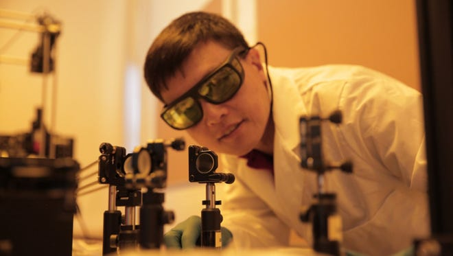 Hongrui Jiang, professor at the University of Wisconsin-Madison, inspects the alignment of a light source to illuminate lateral solar cells. The solar cells developed by Jiang's group harvest almost three times more electricity from incoming light than existing technologies.