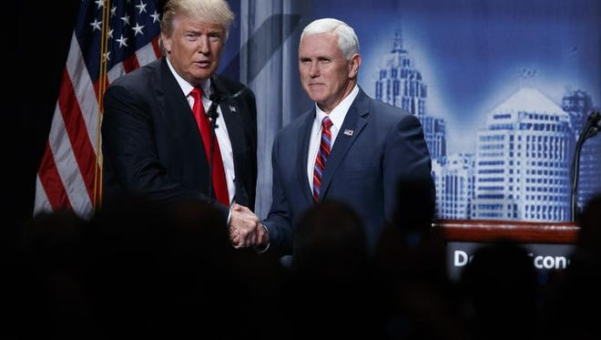 Republican presidential candidate Donald Trump shakes hands with his running mate, Republican vice presidential candidate and Indiana Gov. Mike Pence, as he arrives to give an economic policy speech to the Detroit Economic Club, Monday, Aug. 8.