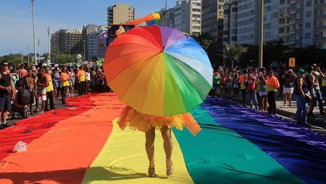 Una persona con una sombrilla participa en la marcha del Orgullo Gay en la playa de Copacabana en Río de Janeiro (Brasil).