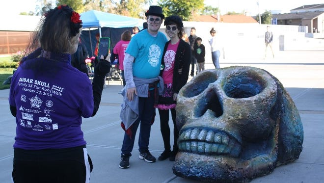 James Clark and Sarah Hunt pause for a photo with a giant skull during the inaugural Sugar Skull Shake Shake in Jeffersonville on Saturday.