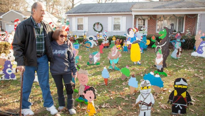 Bill and Judy Sheppard stand  amid the wooden figures on their front lawn.