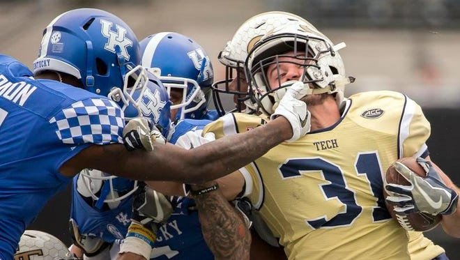 Georgia Tech running back Nate Cottrell, right, is tackled by Kentucky cornerback J.D. Harmon on a kick return during the second half of the TaxSlayer Bowl on Saturday in Jacksonville, Fla. Georgia Tech beat Kentucky 33-18.