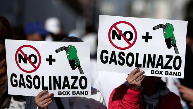 Manifestantes participan en una marcha para protestar por el aumento de la gasolina en el país, por calles de la ciudad de Puebla (México).