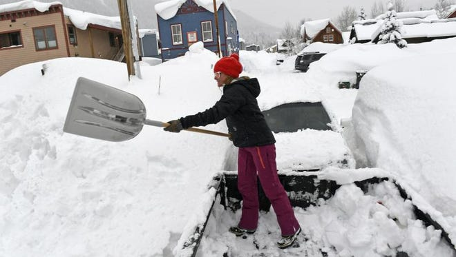 In this Thursday, Jan. 12, 2017 photo, Keitha Kostyk shovels out snow from the bed of her truck to add more snow to the growing pile outside of her home, in Crested Butte, Colo.