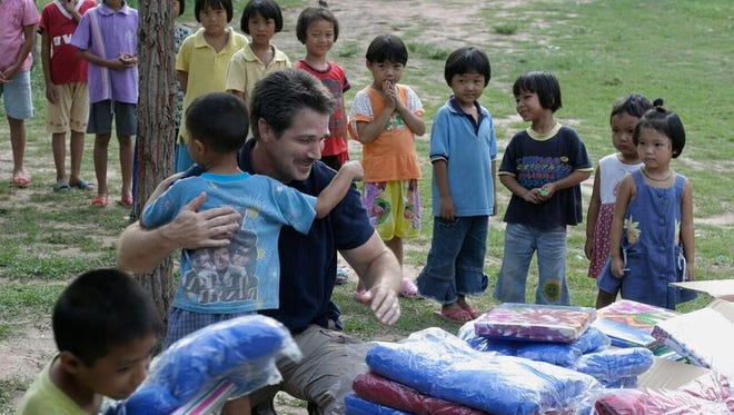 Pastor Kevin Pinkerton from Fremont hands out blankets to orphans whom the church sponsors through the Columbus nonprofit Asia's Hope.