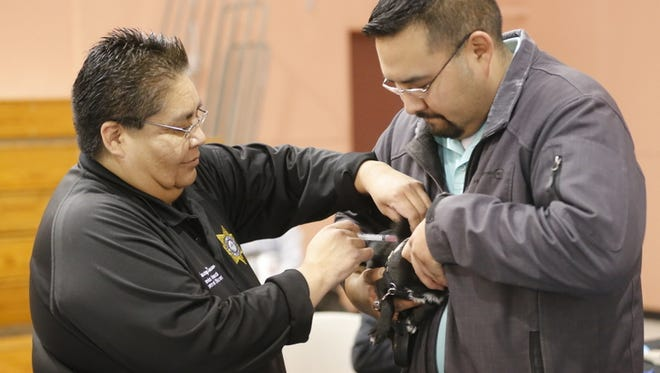 Joseph Begay Jr., right, holds his dog Tico while Stacey Daw, Shiprock senior animal control officer, administers a rabies vaccine at the Walter Collins Center in Fruitland during Saturday's Pet Lovers Stroll event.