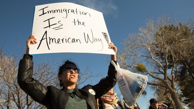 Mary Nuñez holds up a sign during a protest over recent Immigration and Customs Enforcement raids in the U.S., Wednesday, Feb. 15, 2017, in Las Cruces, N.M. The Homeland Security Department said Monday that 680 people were arrested in roundups last week targeting immigrants living illegally in the United States. The figure is far below the totals of similar raids conducted under the Obama administration.  (Josh Bachman/The Las Cruces Sun-News via AP)
