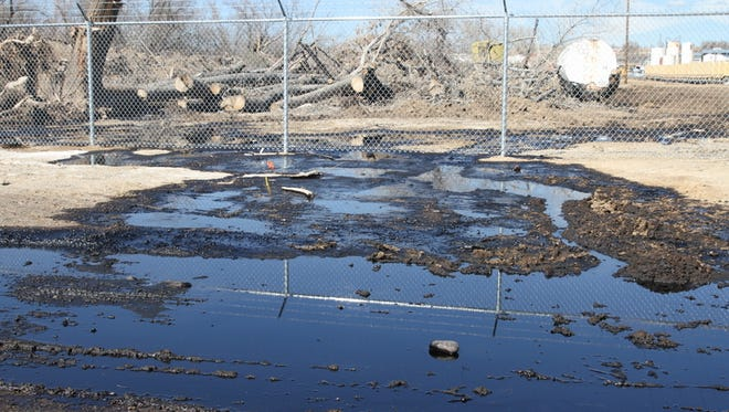 A puddle of spilled dust suppressant spreads across the sand Saturday at an XTO Energy site near county roads 6261 and 6100 in Kirtland.