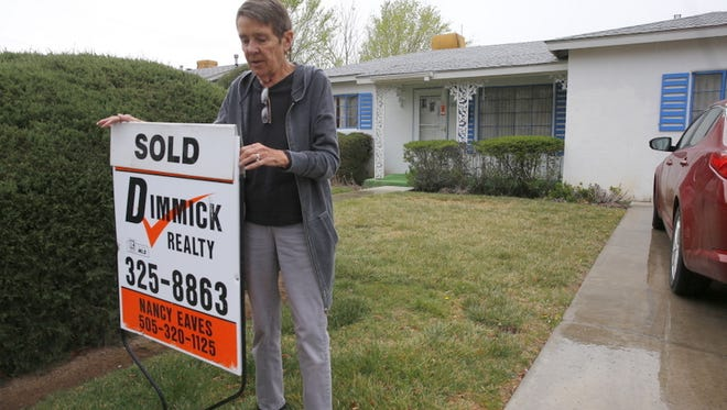 Nancy Eaves, an agent with Dimmick Realty, places a sign on a house located on North Wall Avenue in Farmington Thursday after a sale.