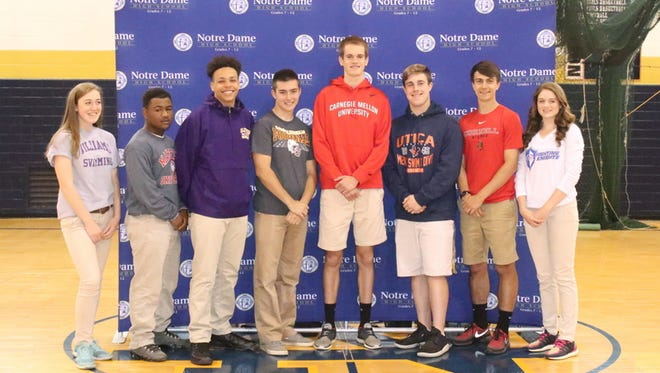 Elmira Notre Dame athletes, from left, Molly Craig, Iman McKay, Derrick Stark, Andrew Spallone, Matt Karee, Justin Larrea, Connor Bayne and Chase Yoder at a signing ceremony May 11 at the high school.