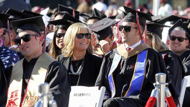 Judy O'Connor, center, sits with her son, MBA graduate Marty O'Connor, during commencement at Chapman University in Orange. Chapman University gave her a surprise honorary degree after she attended every class and took notes for her quadriplegic son while he earned a master's degree.