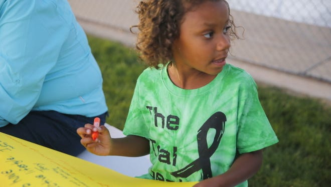 Shia Neil, of Aztec, considers what her pledge to fight cancer will be during Saturday's Relay for Life at the Boys & Girls Clubs of Farmington football field.