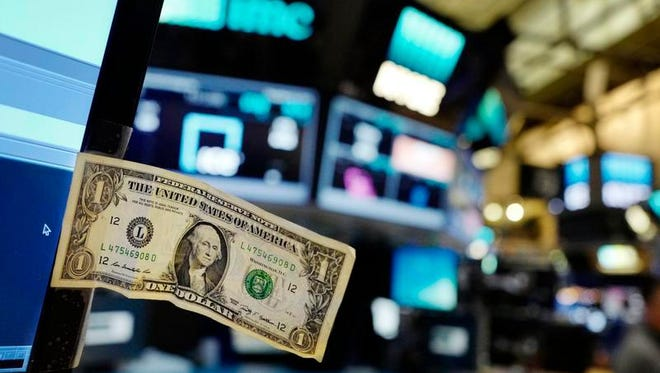 In this Thursday, Dec. 22, 2016, file photo, a dollar bill is taped to a trader's computer screen at the New York Stock Exchange. The good times keep rolling for fund investors. As of late June 2017, nearly every type of fund logged gains over the three months prior, with technology and foreign stock funds among the top performers. Even bond funds are on pace to deliver returns rivaling their best in recent years.