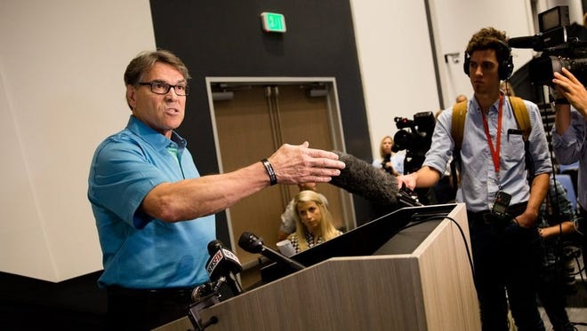 Secretary of Education Rick Perry speaks to the press after touring a manufacturing plant near Houston Friday.
