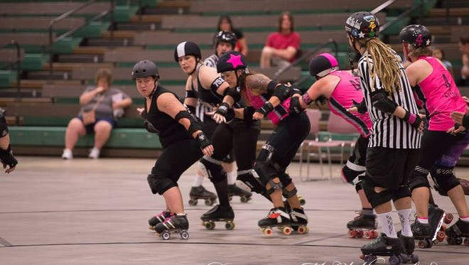 Jamie Overturf, left, plays blocker for the Electric City Roller GrrrlZ. The team plays its next bout Oct. 21.