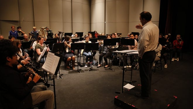Conductor Teun Fetz leads the San Juan College Symphonic Band in a rehearsal Thursday night in anticipation of its concert tonight.