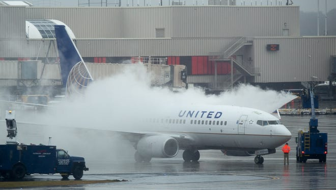 A United Airlines jet is treated with de-icing fluid amid a wintry mix at Atlanta's airport on Dec. 8, 2017.