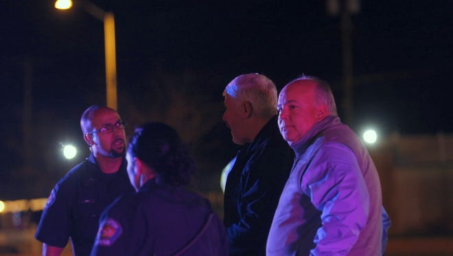 Farmington police Chief Steve Hebbe, second from right, and City Manager Rob Mayes, right, speak with officers after a shooting Wednesday night north of the Bloomfield Highway at Riverstone Drive.